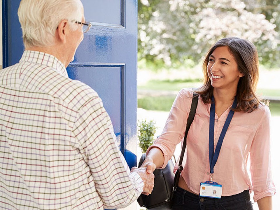 A female social worker greets an elderly man as she walks through his door.