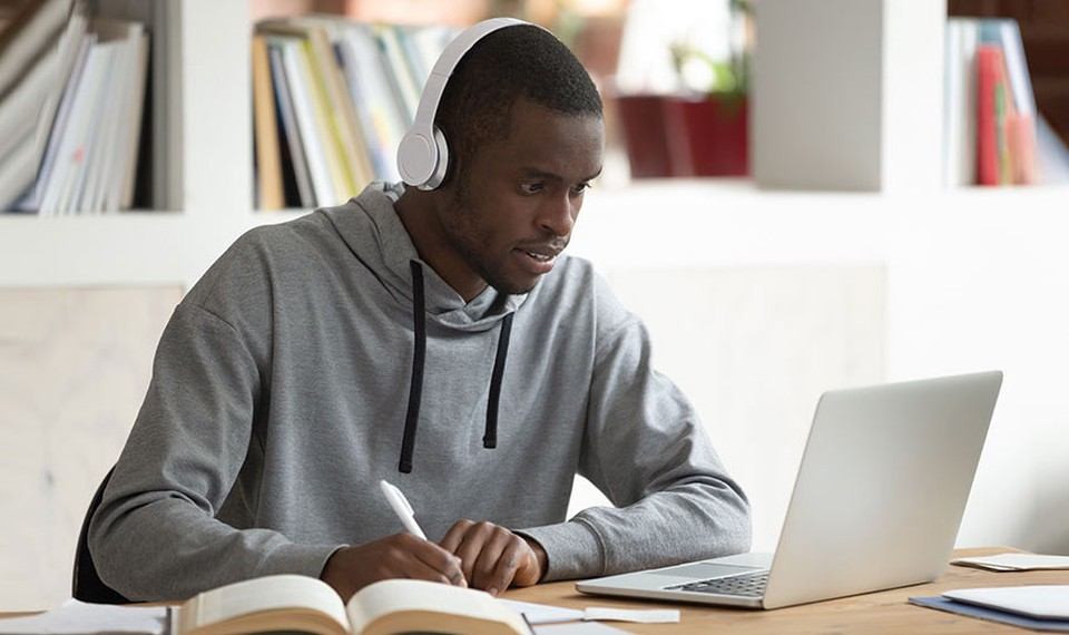 A man surrounded by books completes online courses using a laptop.