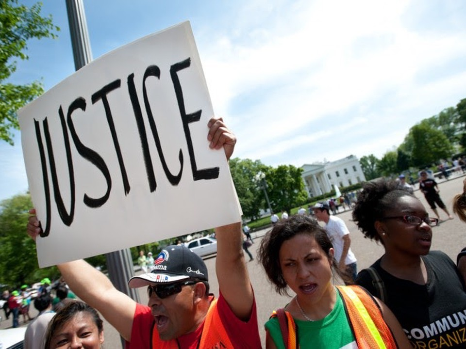 "A protestor in a group holds up a sign reading ""justice."""